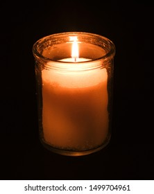 A glass memorial candle on a dark background.