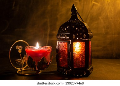Glass with metal candle holder. Evening fire. The atmosphere of comfort and warmth.