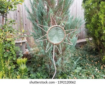 glass and metal sun garden decoration with green plants
