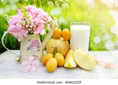 glass of milk, apple fruit and pink flower on white wood table with green grass nature bokeh light background in a garden