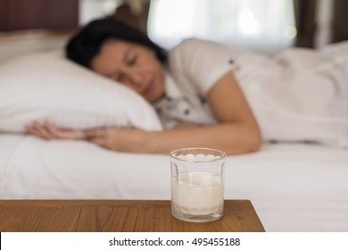 Glass of milk in bedroom and woman sleeping in background. (lens blur effect) concept drink milk for healthy.