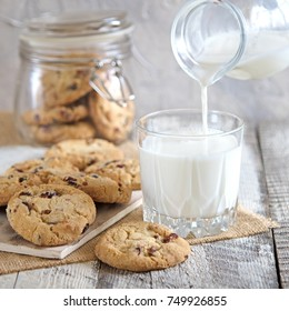 glass of milk and biscuits on wooden grey background