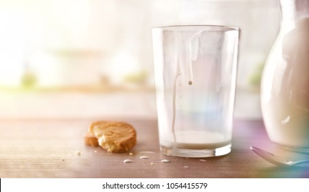 Glass of milk for breakfast finished drinking on brown wooden table in white kitchen. Horizontal composition. Front view