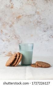 明るい色の田舎的背景に牛乳とクッキーのグラス
