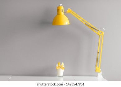 Glass of milk decorated with yellow bowtie standing on table under yellow lamp.