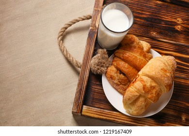 Glass of milk with french croissants on the wooden ructic tray, linen background, copy space