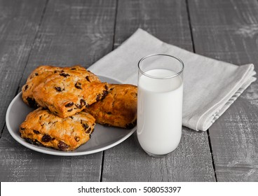 Glass of milk with fresh scones with raisins on wooden table