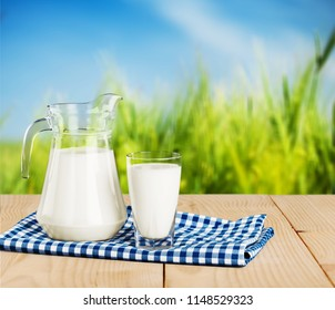 Glass of milk and jug on blurred