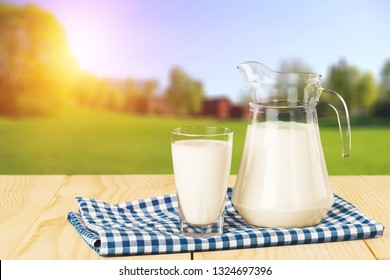 Glass of milk and jug on blurred background