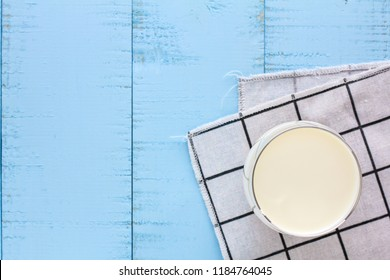 A glass of milk on blue wooden background.