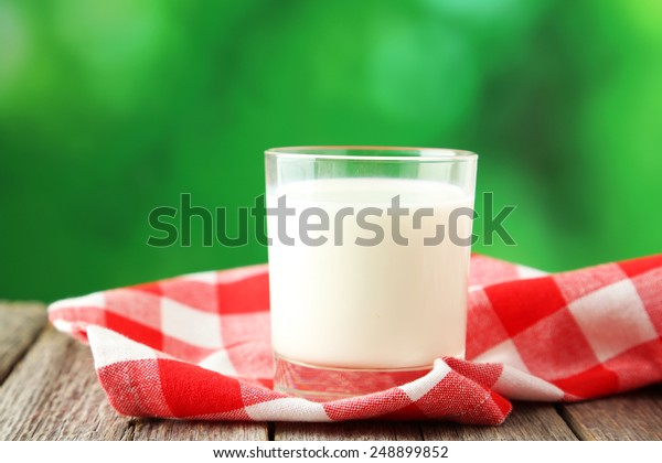 Glass of milk on grey wooden background