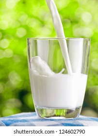 Glass of milk on nature background