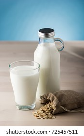 Glass of milk and sack of oats on a wooden table and blue background. daily food
