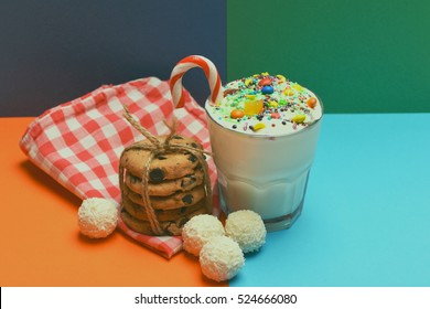 Glass of milk shake with cream, sprinkles, striped caramel candy, colorful dragee, chocolate chip cookies with string, white coconut candies and checkered pink napkin on colorful background