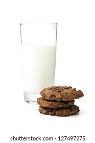 Glass of milk and stacked chocolate chip cookies on white background