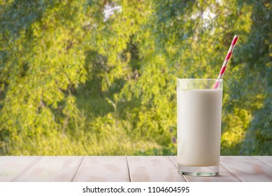 A glass of milk with a straw on a natural green background