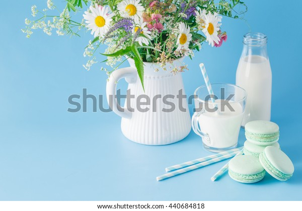 Glass of milk with striped straw and macaroons. Wildflowers in jar