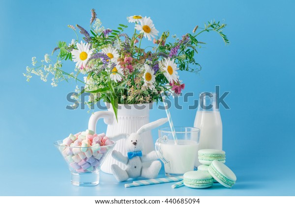 Glass of milk with striped straw sweets and macaroons. Plain blue background and wildflowers, kid breakfast with soft toy