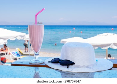 Glass of milkshake, hat and sunglasses on a table with a view of a beach. Rhodes, Greece