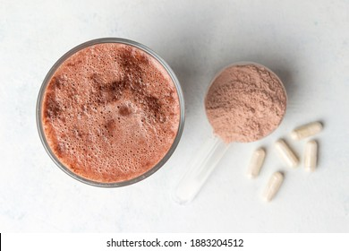 Glass with milkshake of whey protein isolate, protein powder in scoop, white capsules of amino acids and creatine, bodybuilding food supplements on white background, top view, flat lay.