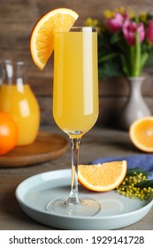 Glass of Mimosa cocktail with garnish on wooden table