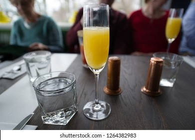 A glass of Mimosa cocktail is sitting o restaurant table during brunch. In the frame there are also glasses of water and Salt & Pepper shakers.