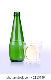 glass of mineral water with lime and green bottle with path