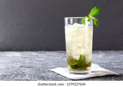 Glass of mint julep served on the napkin.Grey bar table against gray wall.Empty space for your design
