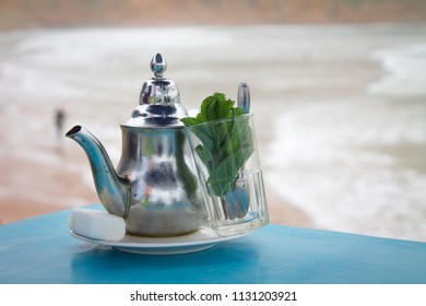 A glass of mint tea with an iron kettle, a sprig of mint and a large slice of sugar. A traditional Berber drink mint tea in the background of the Atlantic Ocean and mountains. Africa, Morocco, Agadir