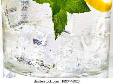 Glass of mojito decorated with a sprig of mint and slice of lemon on white background
