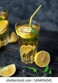 A glass of Mojito or lemonade on a wooden table. Summer chilled refreshing drink with lemon and mint