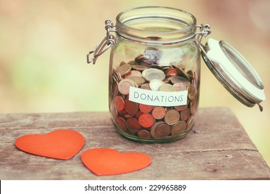 Glass money jar with a label with the word donations on it and two handcrafted wooden heart shapes.
