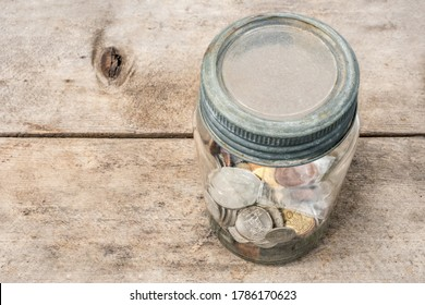 Glass money jar or piggy bank, filled with international coins. Concept for saving money or not trusting banks. Perspective view with focus on coins and jar, soft wood table background. Copy space.