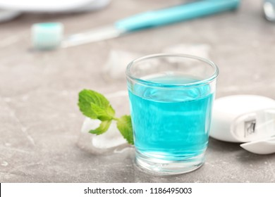 Glass with mouthwash on marble background. Teeth care