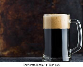 Glass mug of dark beer with foam cap on rustic rusty background