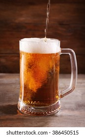 Glass mug of draft light beer on wooden table, close up