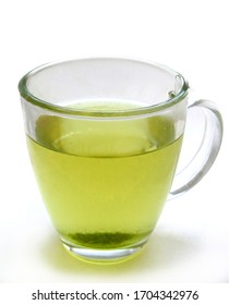 Glass mug filled with warm green tea on white