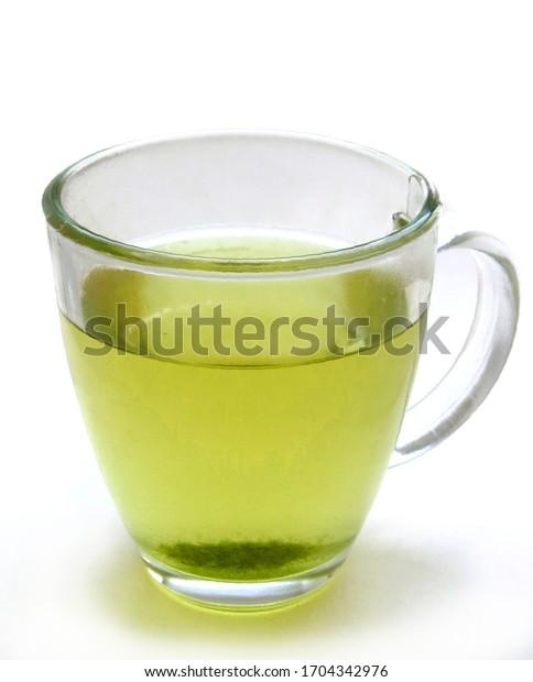 Glass mug filled with warm green tea on white