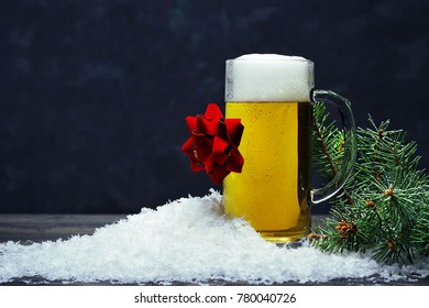 A Glass Mug Of Foaming Light Beer With A Gift Red Bow In The Snow And
