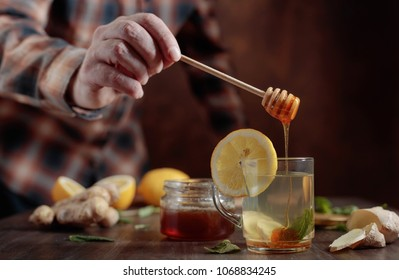 Glass mug of ginger tea with honey , lemon and mint on old wooden table .Man puts a honey in a Cup of tea.  Selective focus .
