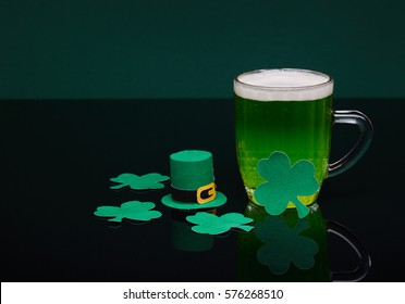 Glass mug of green beer with a decorative shamrocks standing on a black table on a green background. St Patrick's Day.