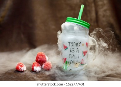 Glass mug with with green strw and fog of dry ice strawberries and kiwi - fruit day