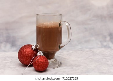 Glass mug of hot cocoa on a cream blurred background with shiny red Christmas baubles