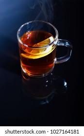 Glass mug with hot tea and lemon on a black and blue background