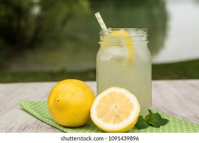 Glass mug of lemonade in summertime outside by the lake