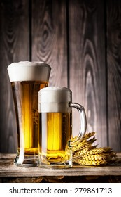 Glass and a mug of light beer with foam and ears on the wooden background