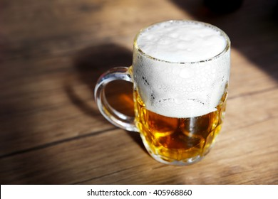 Glass mug of light beer on wooden table