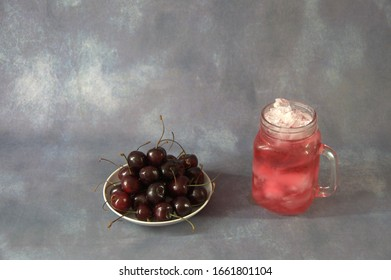 Glass mug of red juice and trill full of ripe cherries on a gray background. Close-up.