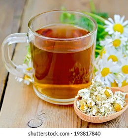 Glass mug with tea, wooden spoon with dry chamomile, a bouquet of fresh flowers on a background of wooden boards