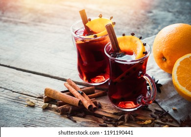 Glass mugs of mulled wine with spices and citrus fruits on wooden table. Copy space for text.